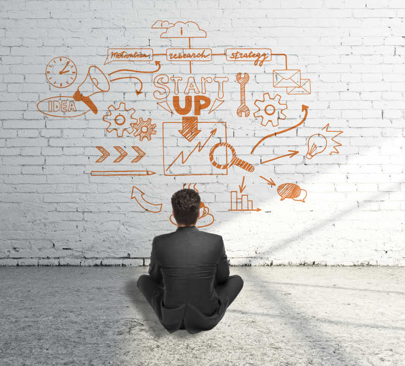 商人坐在水泥地板上看白砖墙上的素描