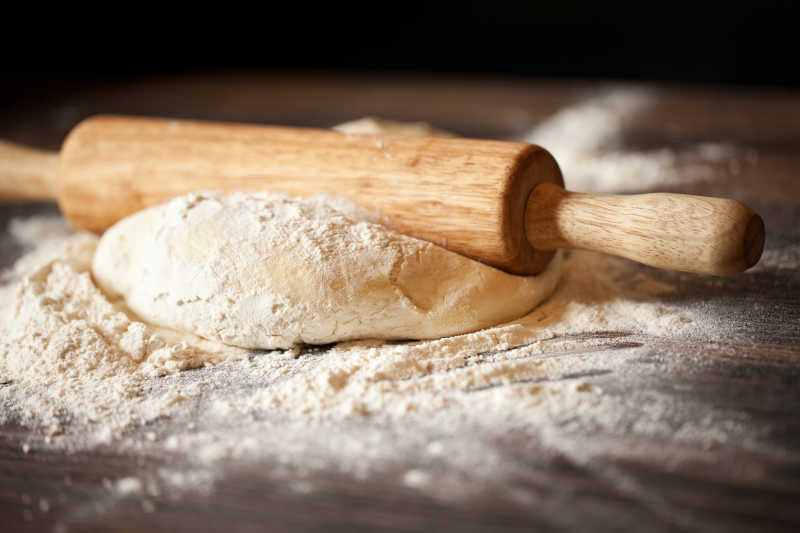 木桌上准备自作面包的面团和擀面杖