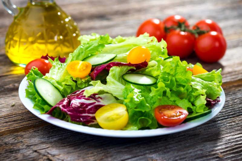 木桌上放在小西红柿旁边的西红柿黄瓜生菜沙拉