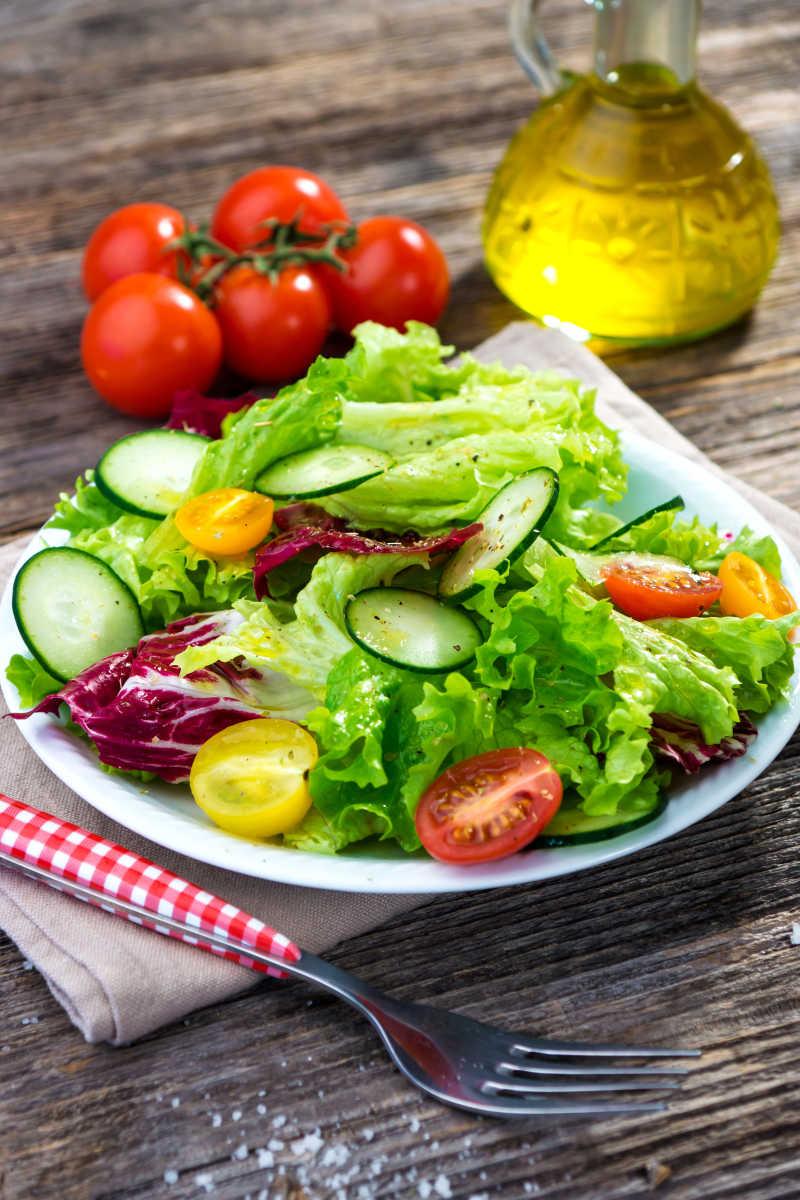 木桌上放在白色盘子里的新鲜美味的小番茄黄瓜生菜沙拉