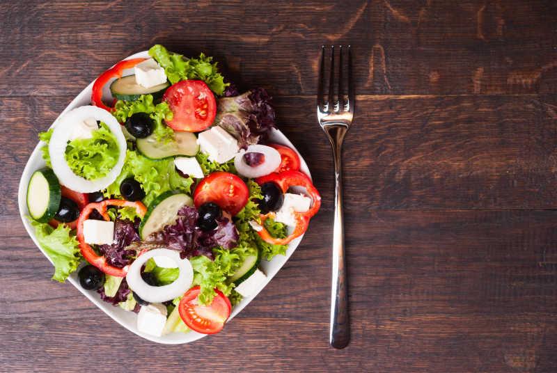 木桌上铁勺旁边的绿色健康沙拉