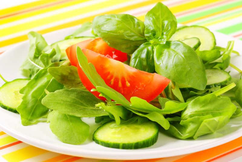 彩色条纹桌子上的西红柿黄瓜生菜沙拉