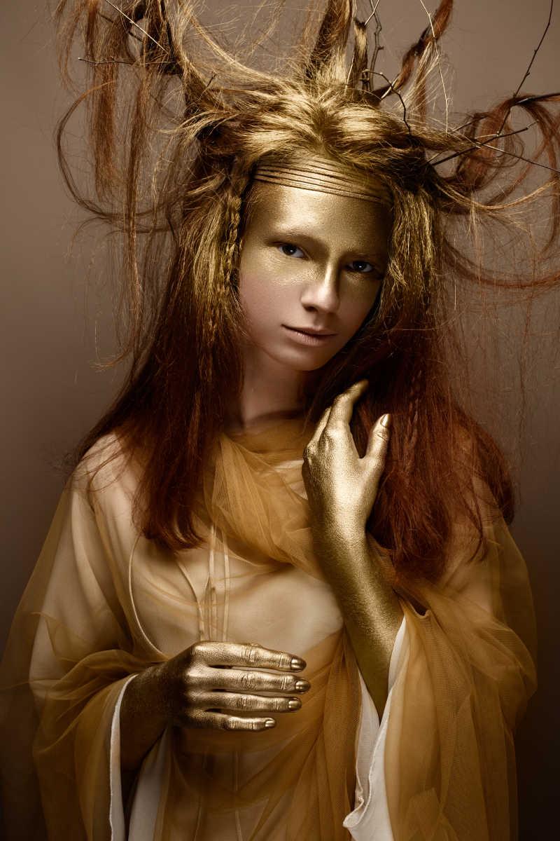 棕色背景前画着金色艺术妆容的美女
