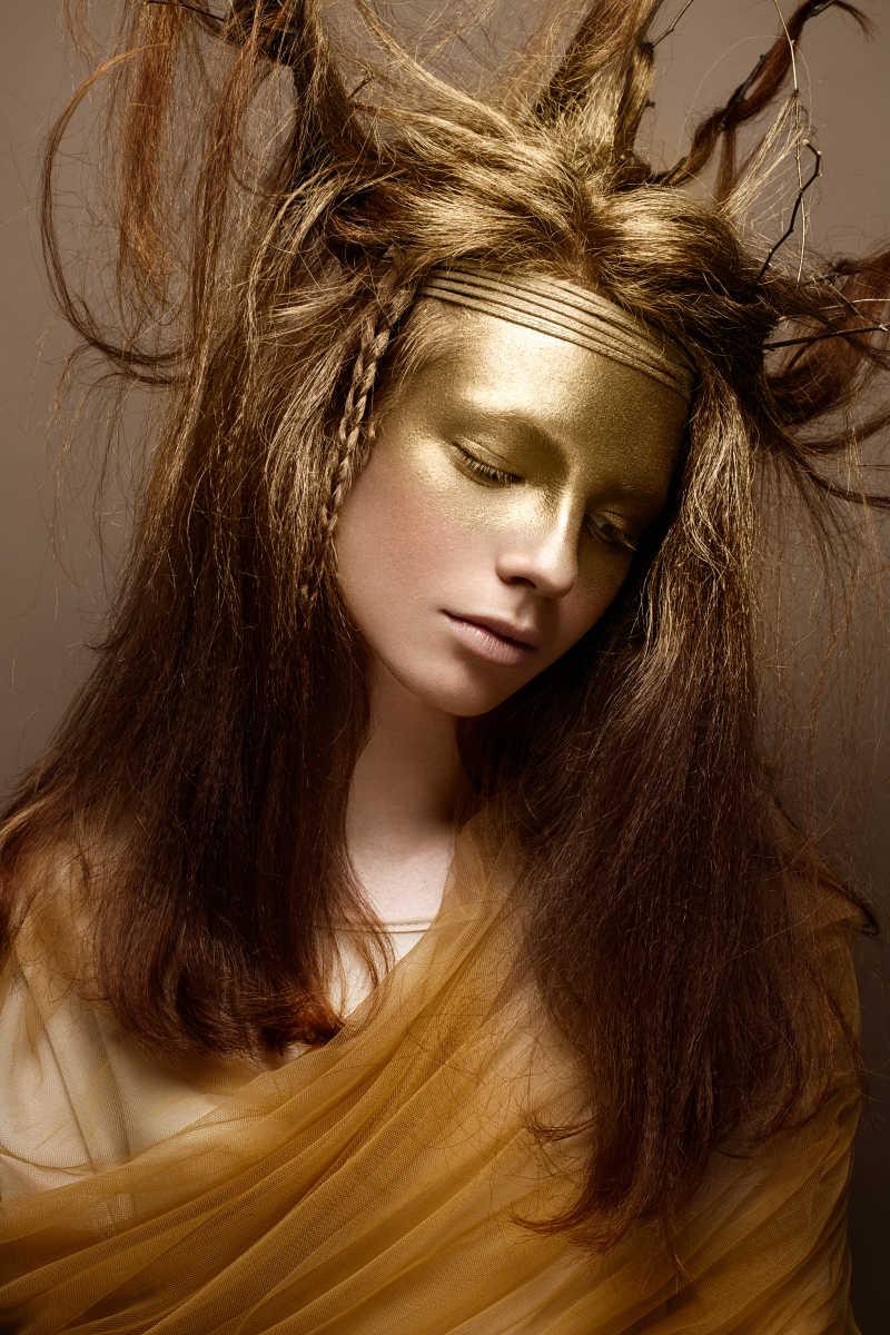 棕色背景前的金色艺术妆容美女