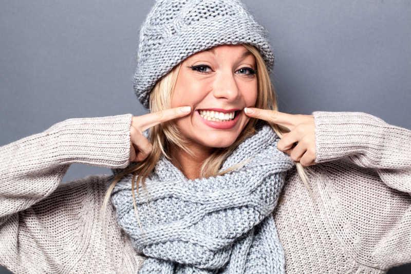 快乐的年轻成熟的金发女人戴着围巾帽子假装微笑着