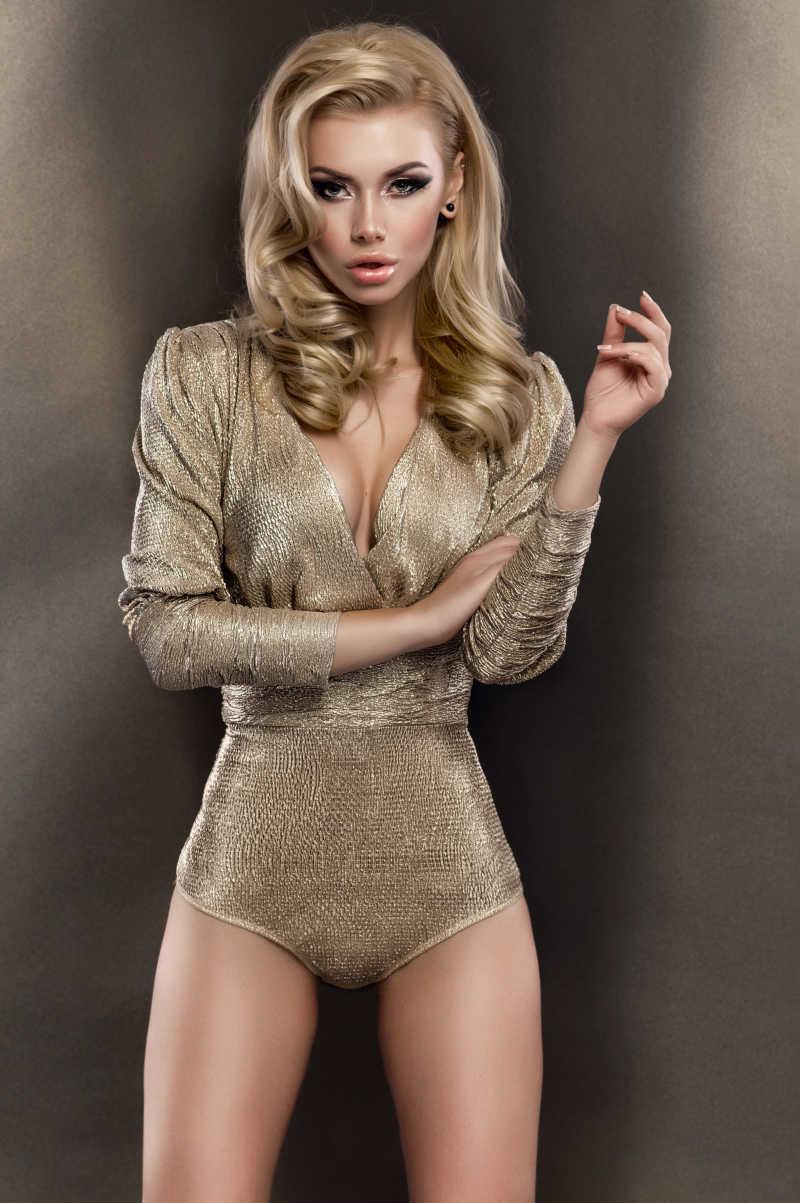 褐色背景下穿着金色紧身衣的金发模特