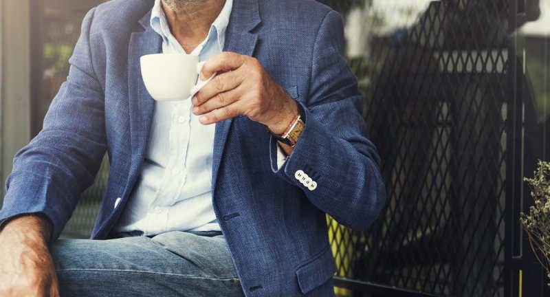 坐在室外喝着咖啡的男性商人
