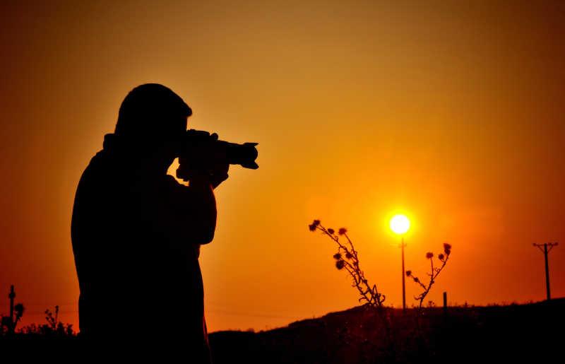 日落下的摄影爱好者剪影