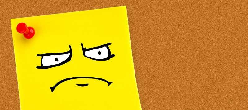 黄色磨砂背景上一张印着表情的黄色便签纸