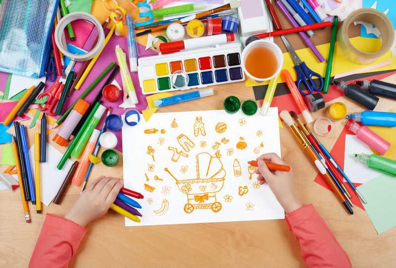 儿童在杂乱的书桌上画婴儿用品