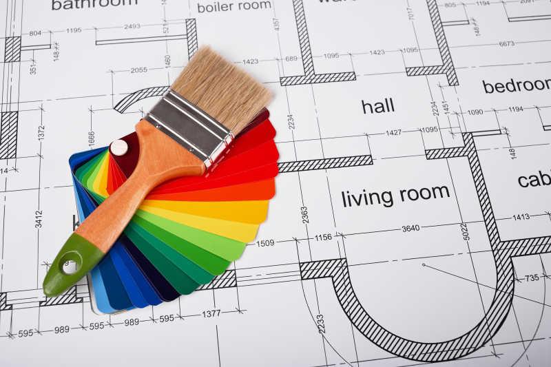 桌子上的建筑平面图设计和彩漆工具