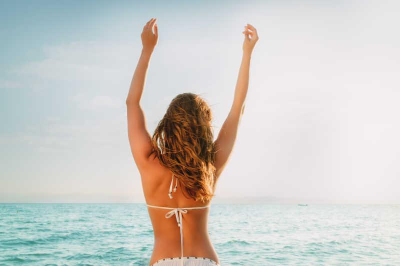 海滩上享受放松的年轻比基尼女孩