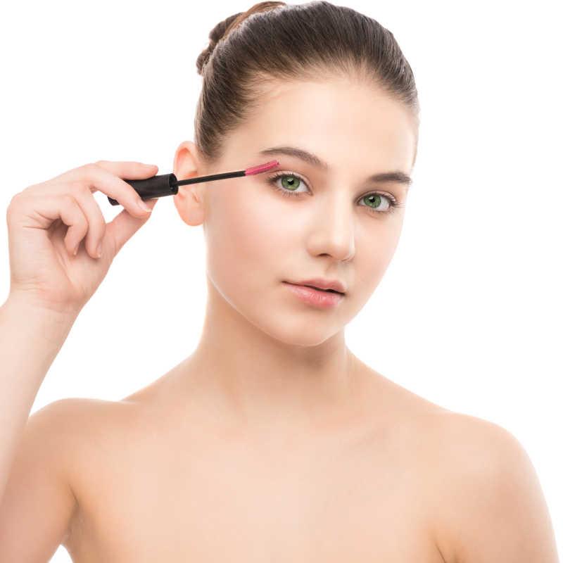 白色背景中美女使用睫毛膏刷化妆
