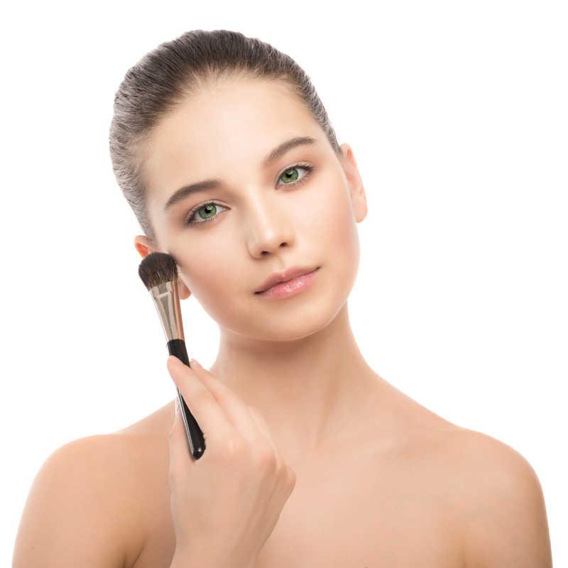 用化妆刷化妆的美女