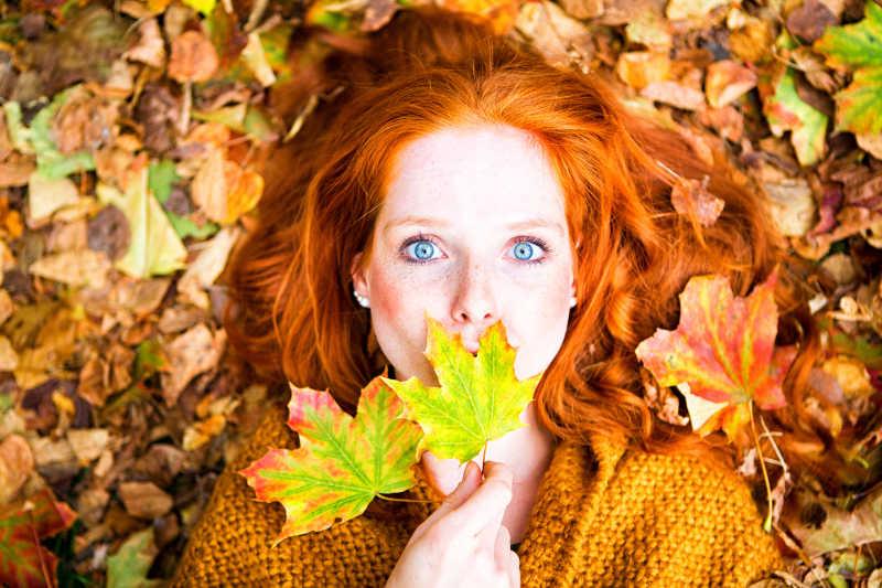 秋季美女躺在落叶上拿着两张枫叶拍照