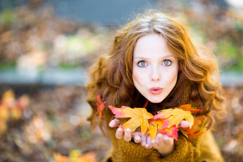 秋季捧着枫叶的女子