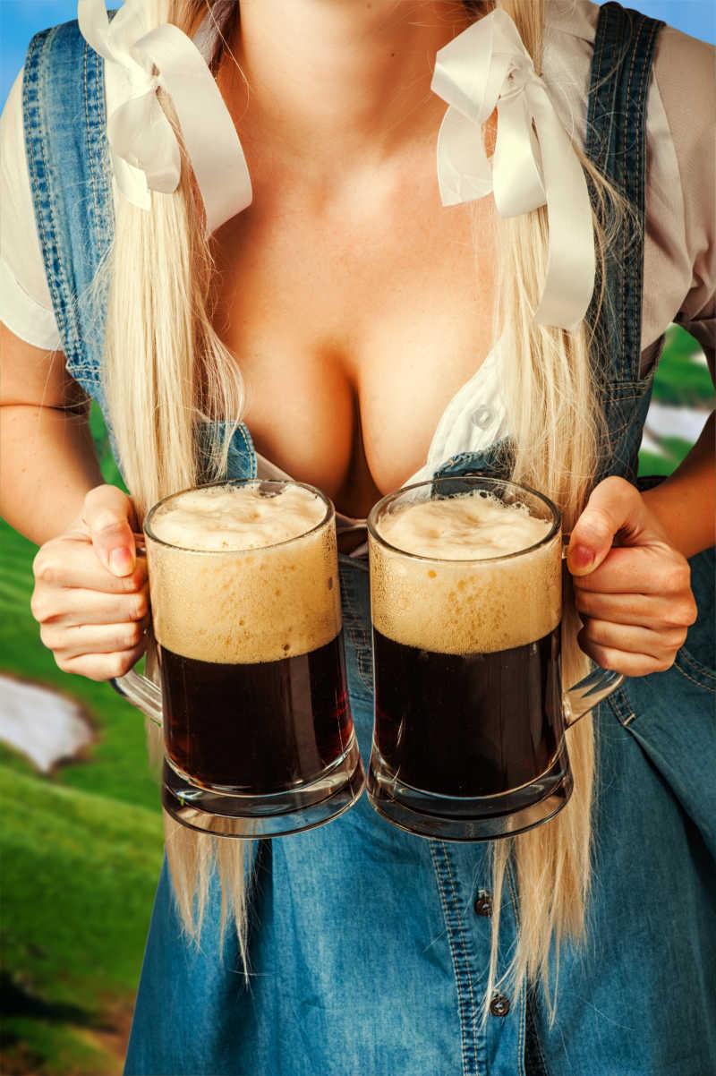 年轻性感啤酒女拿着两个深啤酒杯