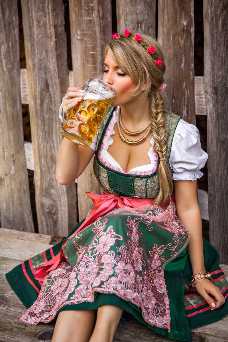穿着裙子的金发女郎喝啤酒