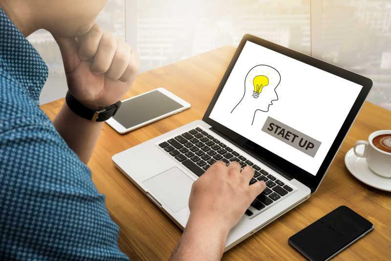 木桌上男人使用笔记本启动创业概念