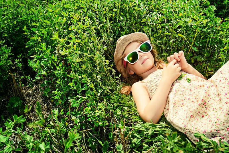阳光下躺在草地上戴着太阳镜的小女孩
