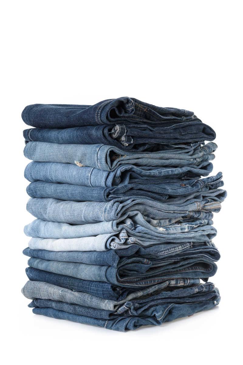 白色背景下堆叠在一起的牛仔裤