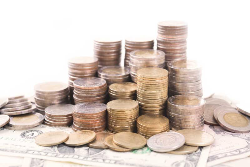 白色背景前堆积的货币和美元
