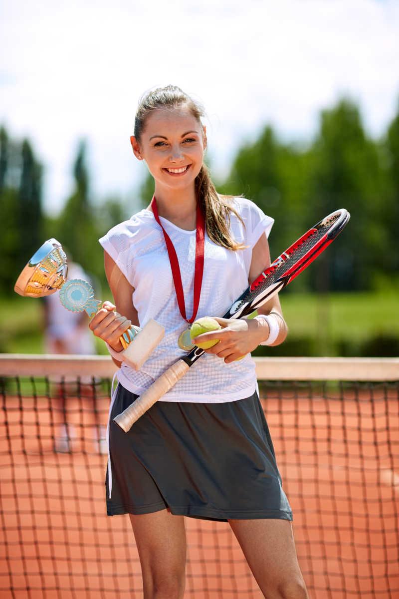 网球女子优胜者在球场上赢得奖杯和奖牌