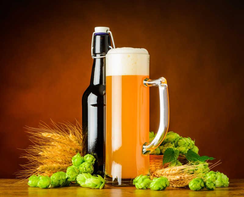 褐色背景下木桌上的一些小麦穗、一瓶啤酒和一杯啤酒