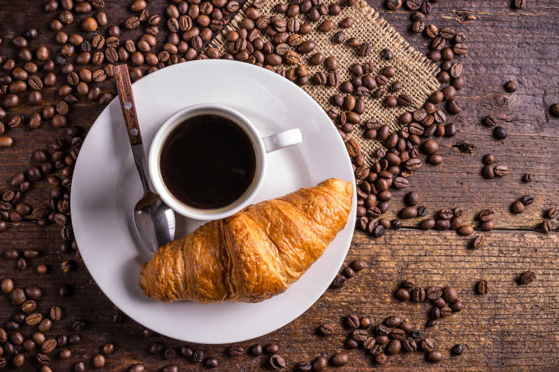 木桌上放在盘子里的面包和咖啡以及咖啡豆
