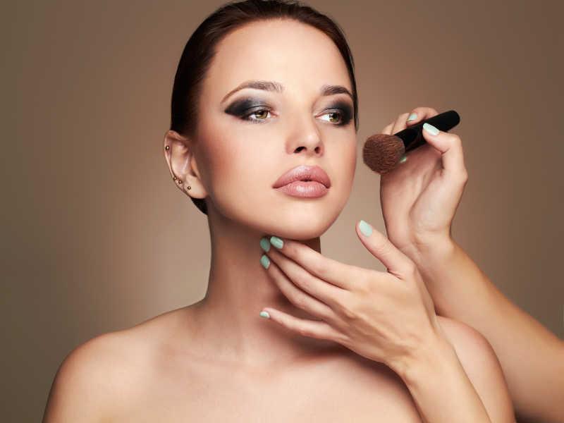 化妆师拿着化妆刷为模特化妆