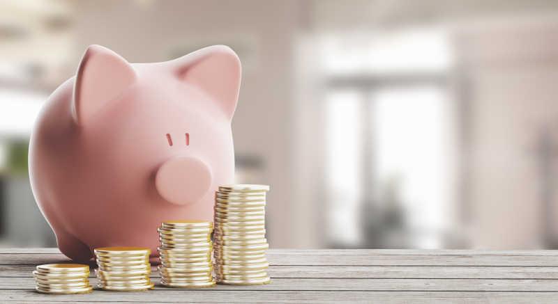 木制桌面上硬币和粉色宝贝猪存钱罐