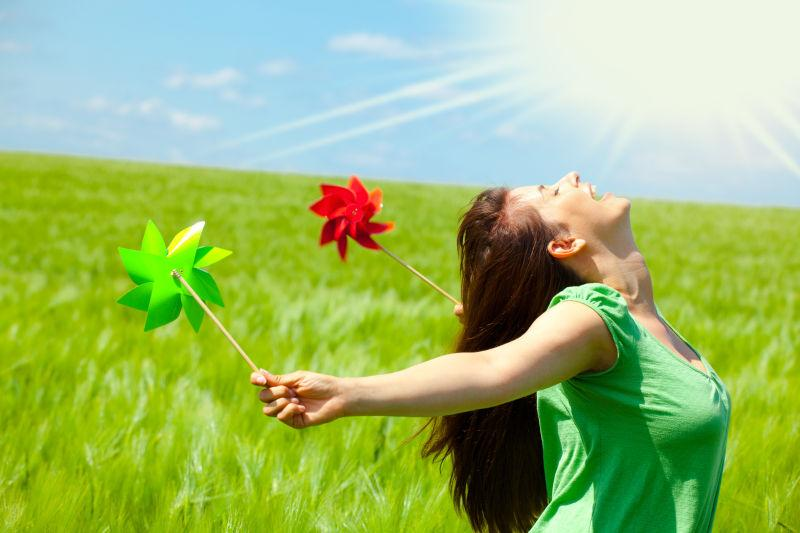 在阳光下双手拿着风车的美女