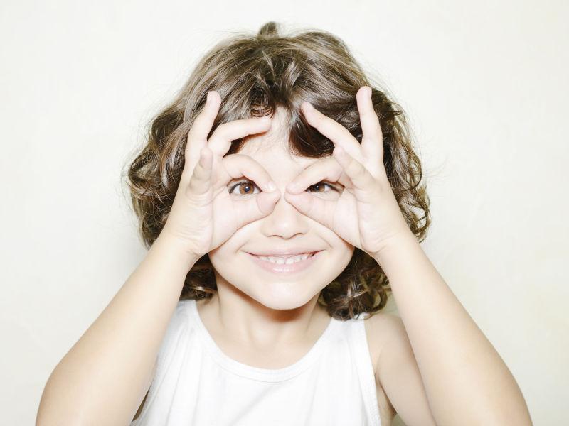 用手做的眼镜的小女孩