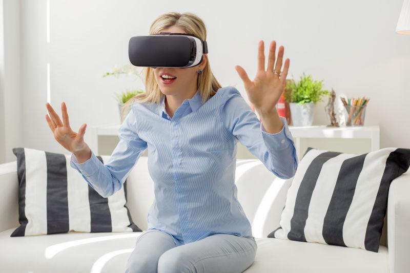白色背景下坐在沙发上戴着3D眼镜-vr眼镜伸出双手的人