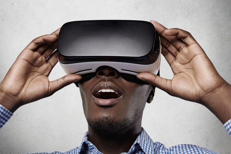 白色背景下双手扶着3D眼镜-vr眼镜做出吃惊表情的男人