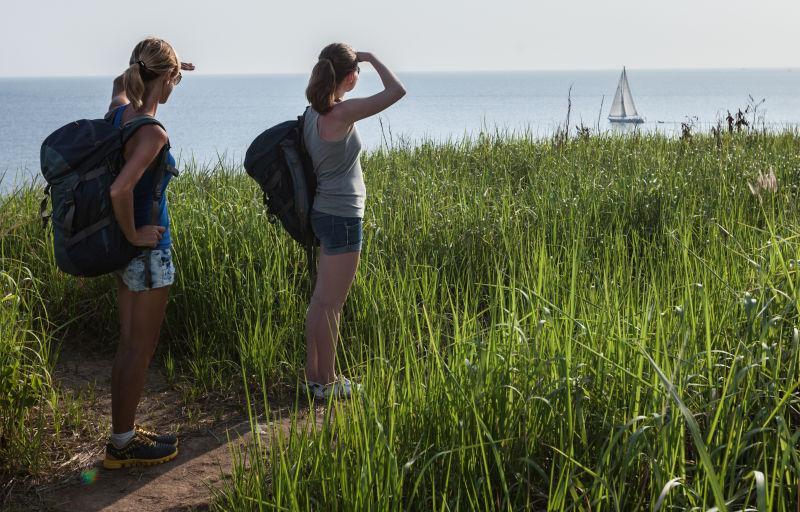 田野里的两名徒步旅行者看向海上的船