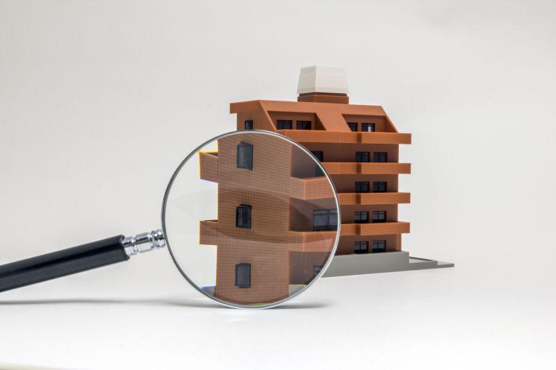 用放大镜观看建筑公寓模型