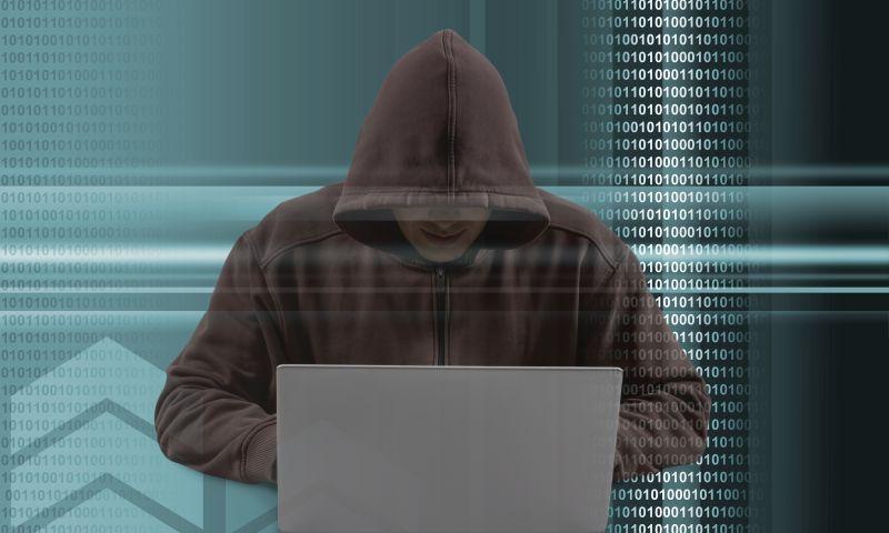 穿着黑色卫衣的黑客在操控笔记本