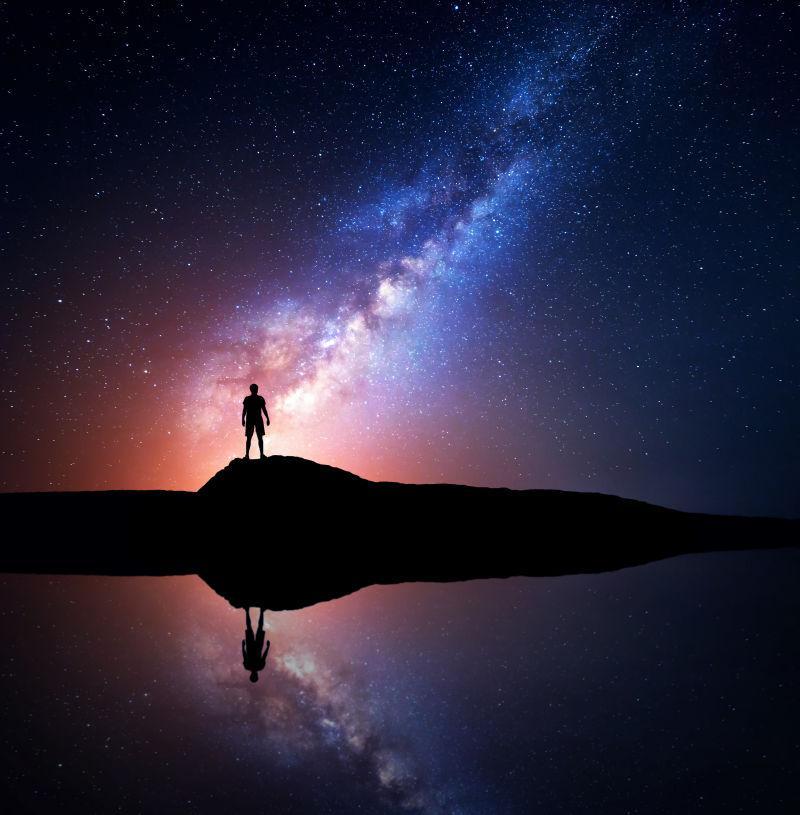 一个人站在湖边的山上的身影