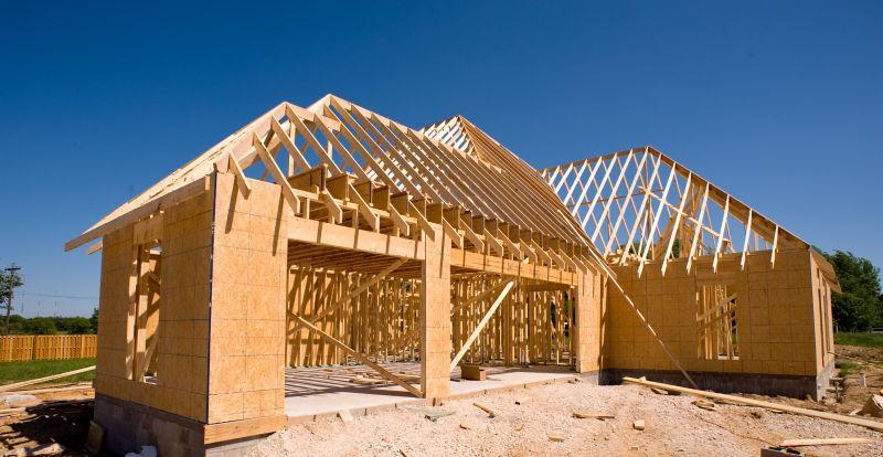 蓝天下黄色土地上正在建设的木头房子