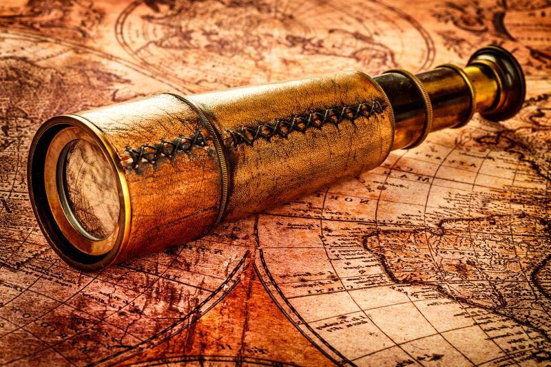 古董望远镜位于古代世界地图上