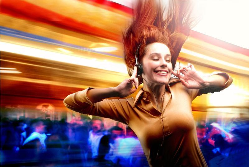 金黄色灯光的酒吧里戴着耳机跳舞的美女