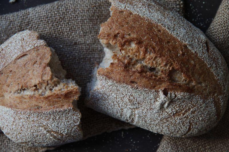 桌子上的一个掰成两瓣的手工面包