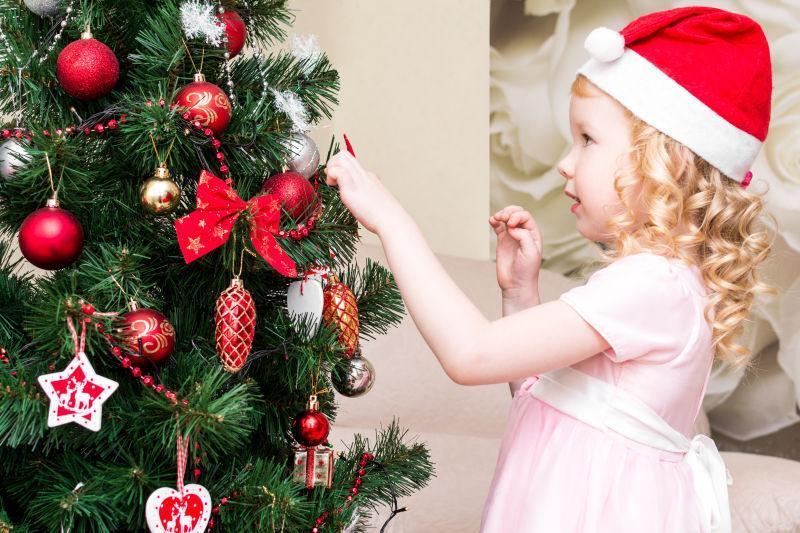 戴着圣诞帽子穿粉色裙子的小女孩在圣诞树下