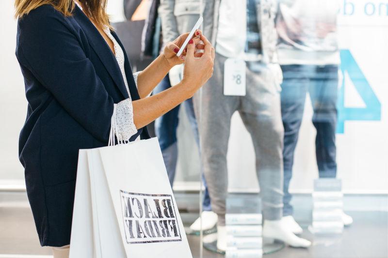 商场背景下拎着购物袋使用智能手机的美女