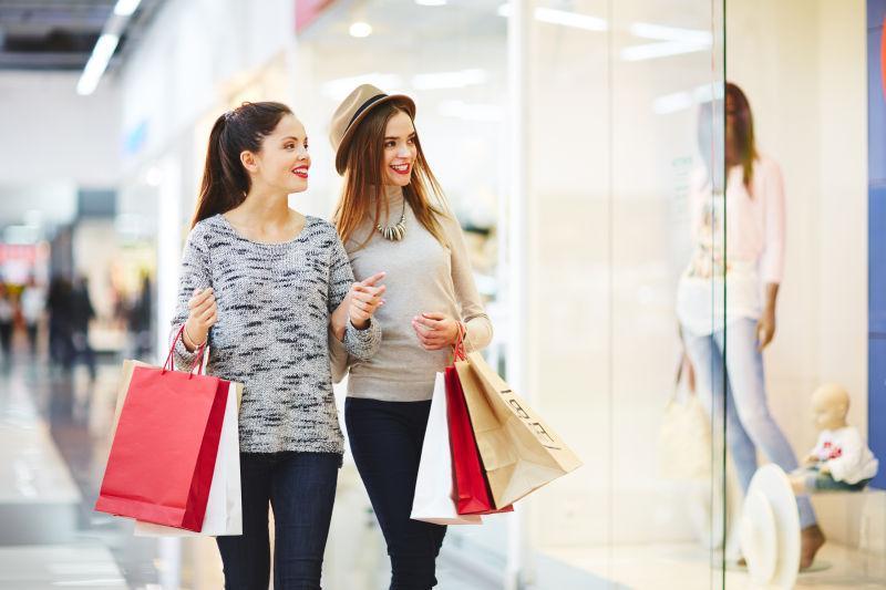 商场背景下拎着购物袋开心的交谈的美女们