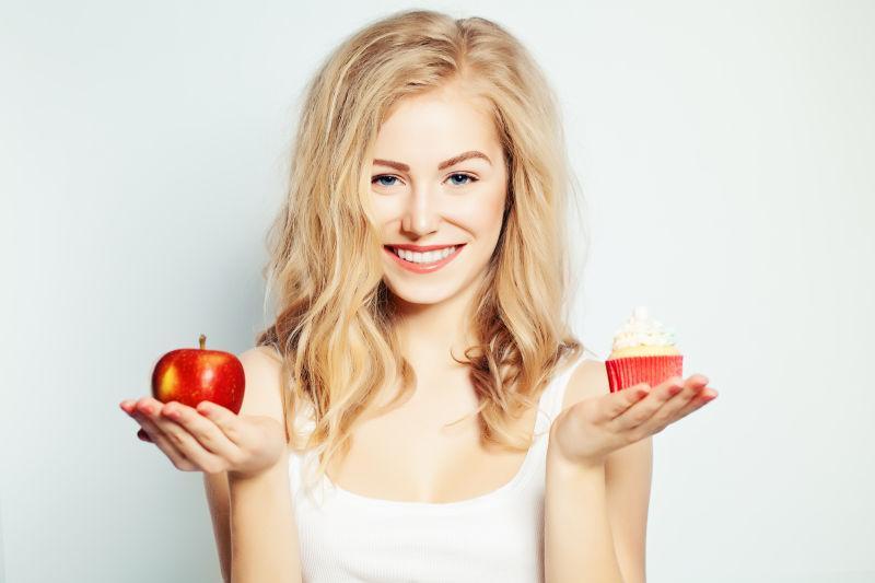 拿着蛋糕苹果的金发美女的艰难选择
