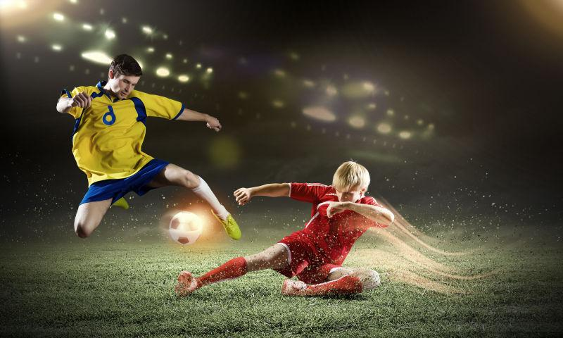黑色背景下足球场上的足球比赛中两个足球运动员在抢球