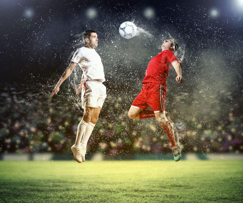 黑色背景下的足球场上的两个足球运动员在抢球