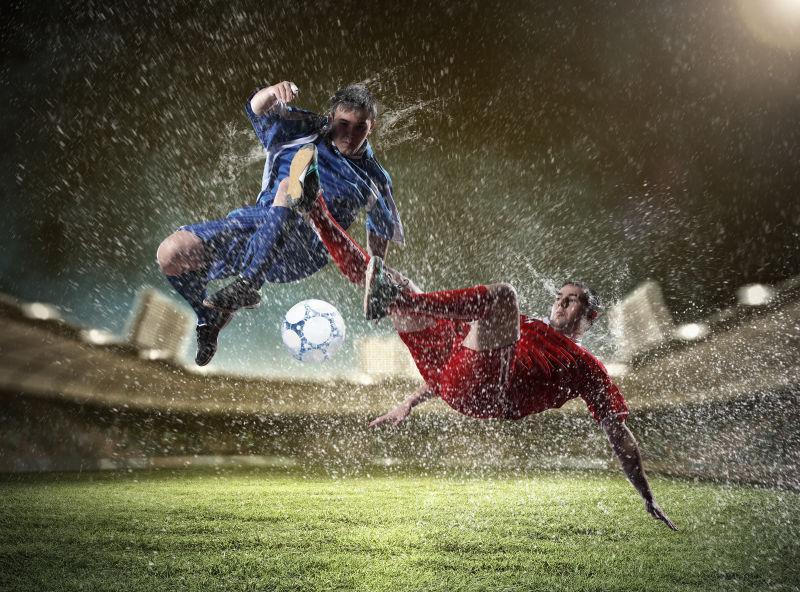 夜晚的足球场上穿着红色和蓝色球服的两个足球运动员在抢球